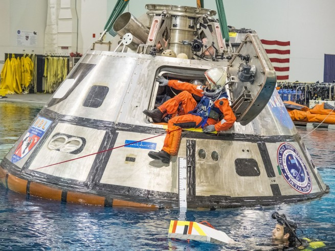 Astronauts train for egress from the Orion spacecraft at Johnson Space Center. The exercise device selected for flight aboard Orion will fit in the step area just below the hatch. Its goal will be to preserve the astronauts' strength and fitness in order successfully make the somewhat strenuous water egress from the spacecraft in case of emergency. Photo Credit: NASA posted on SpaceFlight Insider