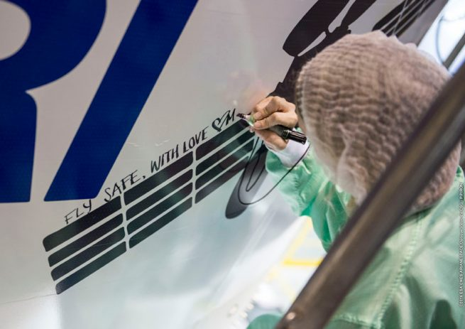 "A BRIsat satellite team member adds a ""personal touch"" to Ariane 5's payload fairing."