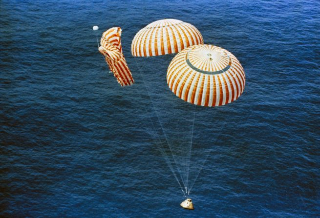 The command module splashes down two of its three chutes deployed. Photo Credit: NASA