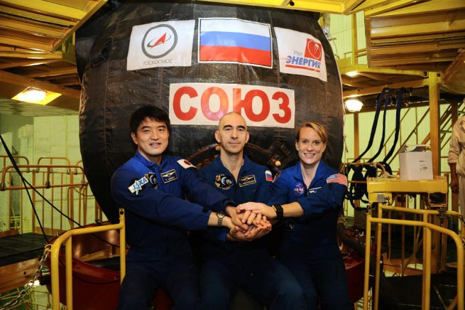 From left to right: astronaut Takuya Onishi of the Japan Aerospace Exploration Agency (JAXA), cosmonaut Anatoly Ivanishin of Roscosmos and NASA astronaut Kate Rubins pose for pictures in front of their Soyuz MS-01 spacecraft. Photo Credit: RKK Energia
