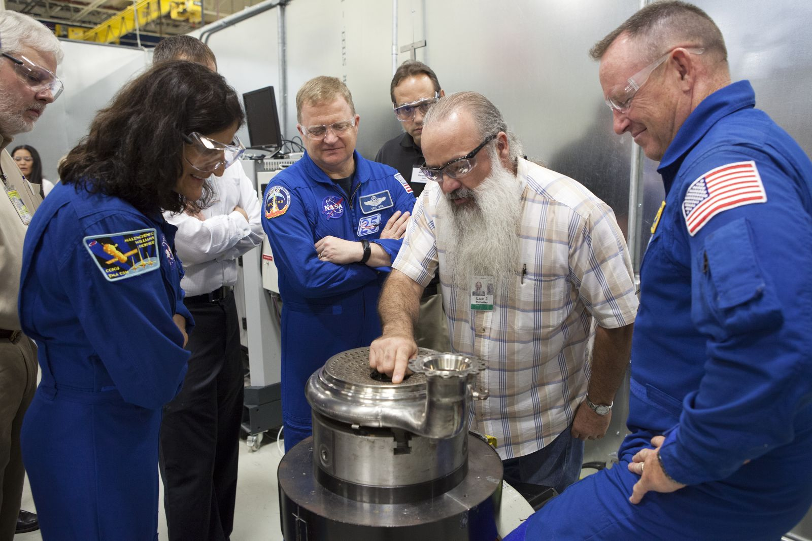 "NASA astronauts Suni Williams, from left, Eric Boe and Barry ""Butch"" Wilmore listen as an Aerojet Rocketdyne engineer details the injector plate of an RL10 engine."
