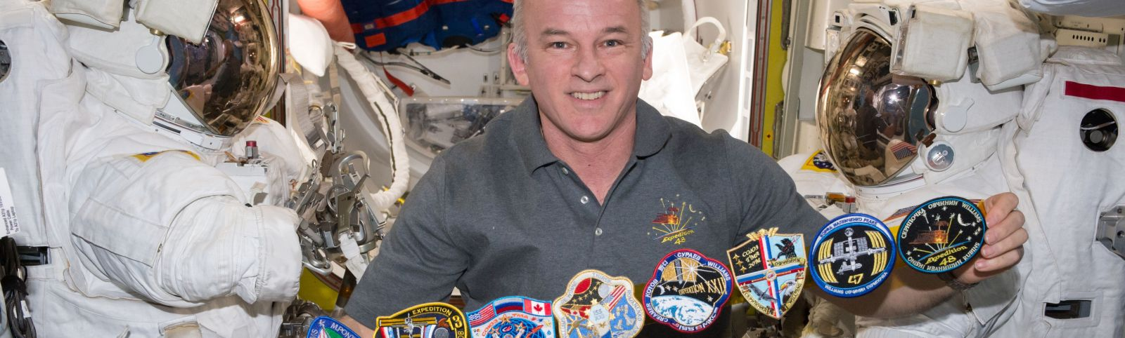 Jeff Williams shows off his mission patches. Click for full image. Photo Credit: NASA