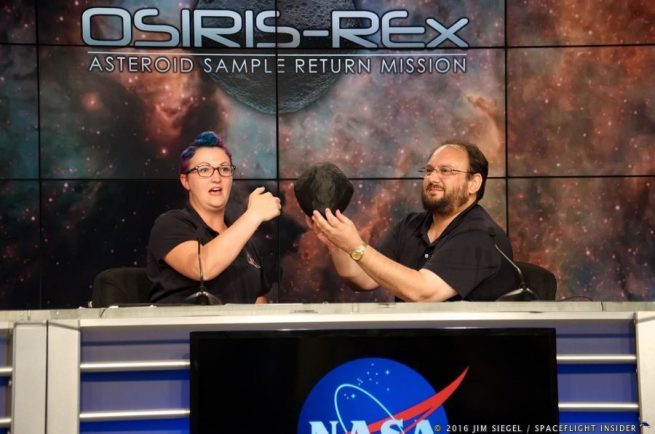 Christina Richey (left), OSIRIS-REx deputy program scientist at NASA Headquarters in Washington, and Jason Dworkin, OSIRIS-REx project scientist at Goddard, demonstrate with a model of the Astroid Bennu how the OSIRIS-REx mission vehicle will approach the astroid, scan its surface, and eventually perform a 3-second touch down to retrieve a sample of surface material. Photo Credit: Jim Siegel / SpaceFlight Insider