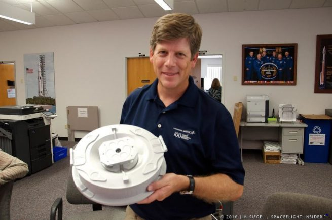 Gary Napier with Lockheed Martin holds a full scale model of the sampler head that will be extended on a robotic arm for a 5-second touchdown of the surface of astroid Bennu, for collection of the asteroid surface material. Photo Credit: Jim Siegel / SpaceFlight Insider