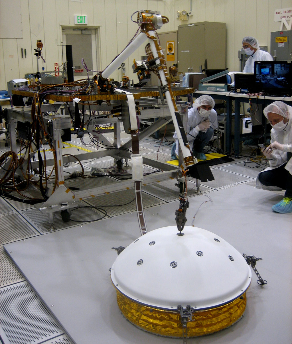 This image shows testing of InSight's robotic arm inside a clean room at NASA's Jet Propulsion Laboratory, deploying a test model of a protective covering for SEIS.