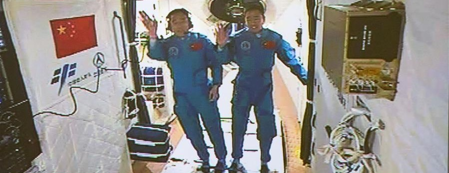 Jing Haipeng (left) and Chen Dong (right) wave to ground controllers after entering Tiangong-2.