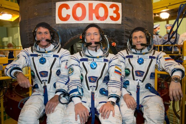 Expedition 49 flight engineer Shane Kimbrough of NASA, left, Soyuz commander Sergey Ryzhikov, center, and flight engineer Andrey Borisenko of Roscosmos, right, pose for pictures, in their Sokol launch and entry suits, in front of their Soyuz MS-02 spacecraft during their first check dress rehearsal activities, Saturday, Oct. 8, 2016 at the Baikonur Cosmodrome in Kazakhstan.