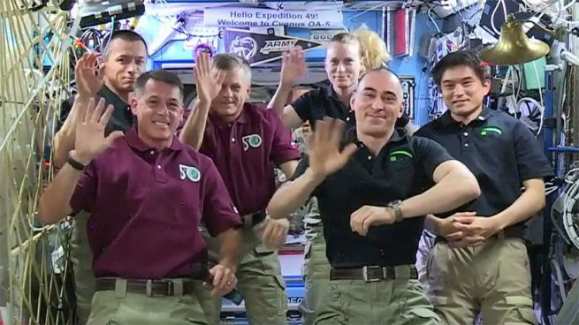 The six Expedition 49 crew members wave to mission controllers moments after cosmonaut Anatoly Ivanishin (right foreground) swapped command with NASA astronaut Shane Kimbrough (left foreground) during a traditional Change of Command Ceremony.