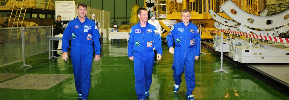 Expedition 49 flight engineer Shane Kimbrough of NASA, left, Soyuz commander Sergey Ryzhikov, center, and flight engineer Andrey Borisenko of Roscosmos, right, at the launch vehicle processing facility in Baikonur.