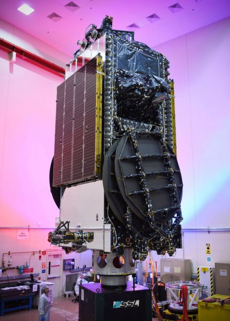 The EchoStar XIX, with its antennas and solar arrays stowed, sits on a vertical stand prior to fairing encapsulation. Photo credit: SSL