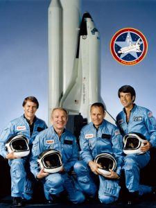 The STS-5 crew in their light blue flight suits with helmets pose for their crew portrait.
