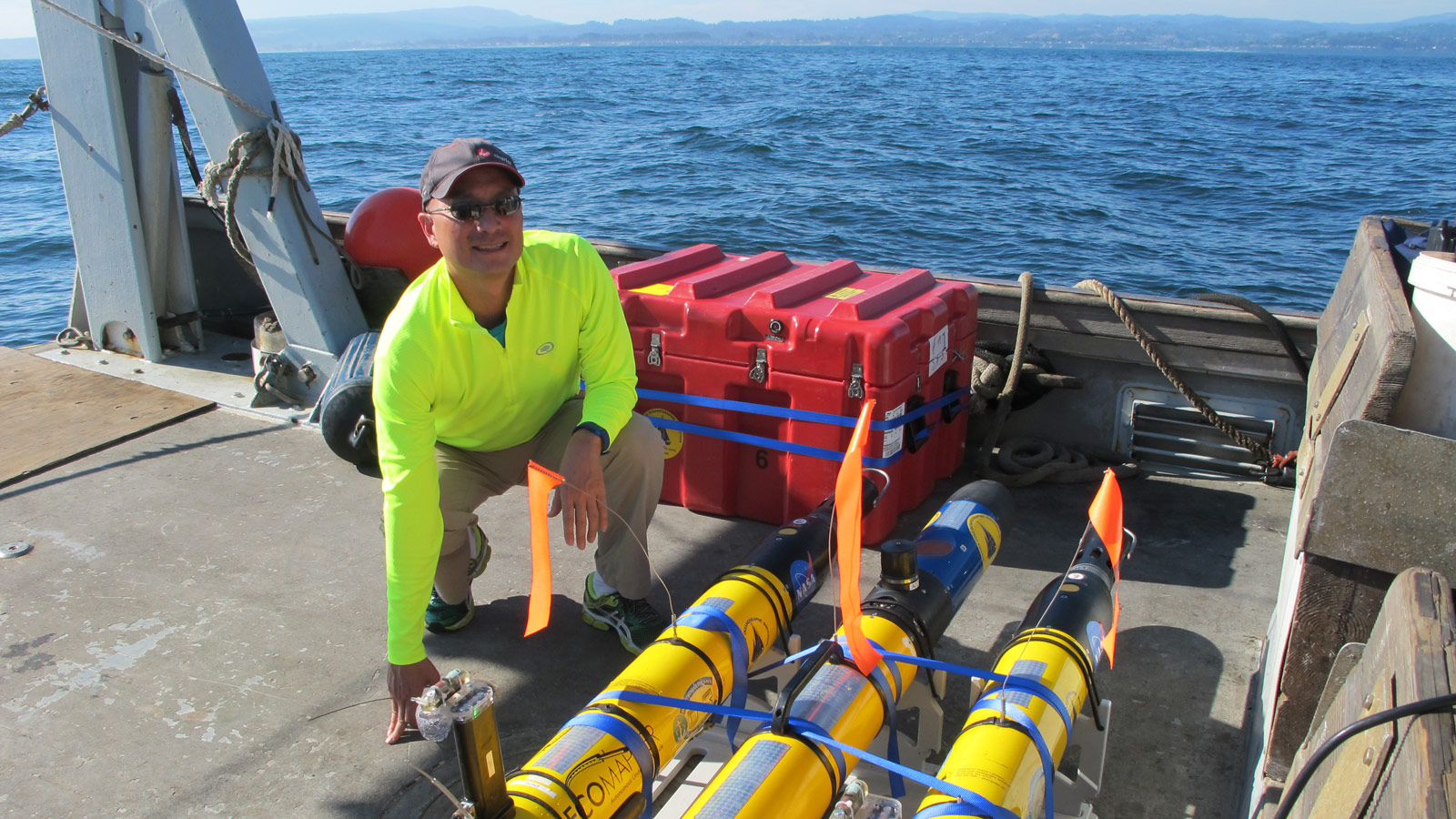 JPL's Steve Chien with several of the underwater drones used in a research project earlier this year. Chien, along with his research collaborators, are developing artificial intelligence for these drones. Photo Credit: NASA / JPL-Caltech.