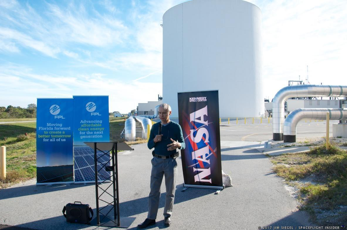 KSC's Ismael Otero explains how the 2.8 million gallon thermal energy storage tank in the background lowers energy costs within the complex by storing water that is chilled during off-peak nighttime hours and later used to cool buildings during the daytime. The project was originally proposed by an intern a few years ago and construction was completed last Fall. The large silver pipes shown behind Otero on either side of the tank carry the chilled water to and from the chiller building located about just a few yards to his right. Photo Credit: Jim Siegel / SpaceFlight Insider
