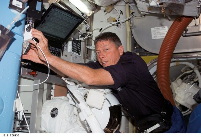Mike Fossum, STS-121 mission specialist, works in the Quest Airlock of the International Space Station while Space Shuttle Discovery was docked with the station. An Extravehicular Mobility Unit (EMU) spacesuit is visible at bottom.