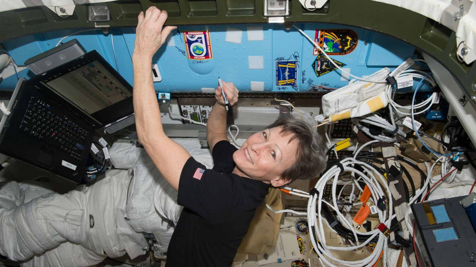 Peggy Whitson signs her name on the wall of the ISS