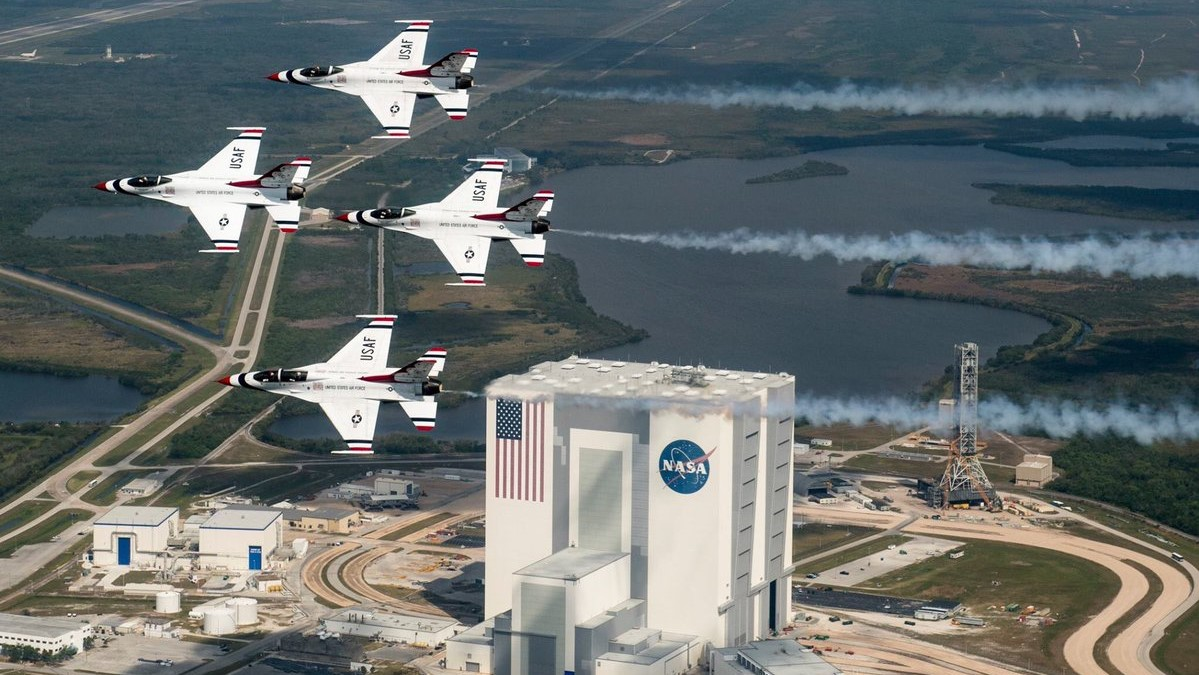 The Thunderbirds, with Buzz Aldrin in the back seat of one of the Lockheed F-16D Fighting Falcons, fly past the Kennedy Space Center
