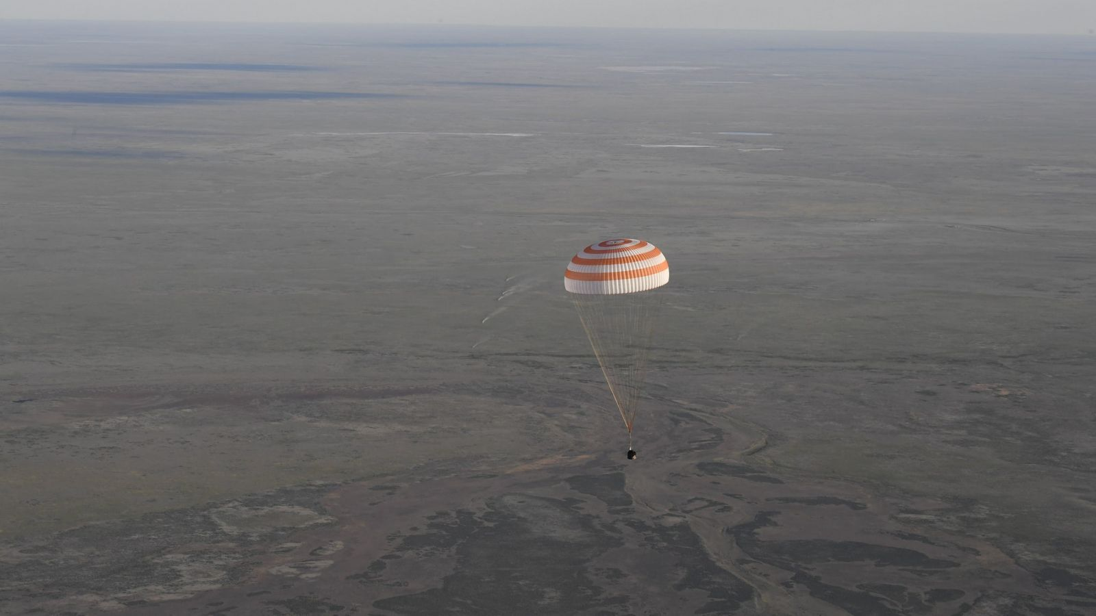 A Soyuz MS capsule descends toward the ground at the Kazakh Steppe. Two members of the Expedition 51 crew returned to Earth on June 2, 2017. Photo Credit: Stephane Corvaja / ESA