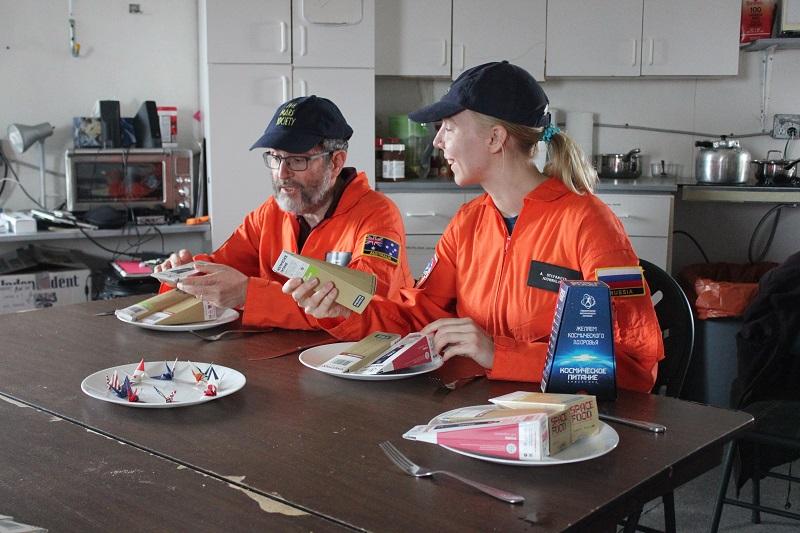 Jonathan Clarke and Anastasiya Stepanova prepare to eat Russian space food courtesy of Spacefood Laboratories. Photo Credit: Mars Society