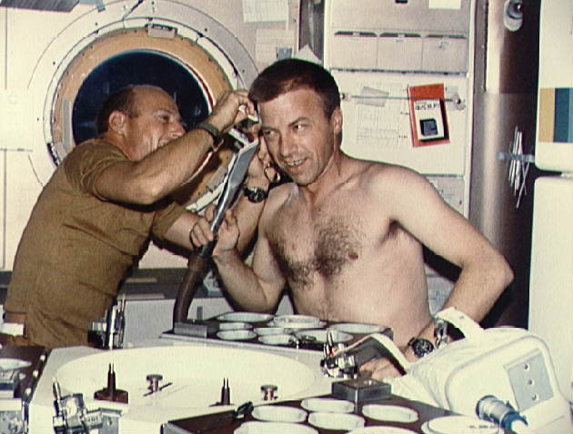 Pete Conrad trims Paul Weitz's hair aboard Skylab 2