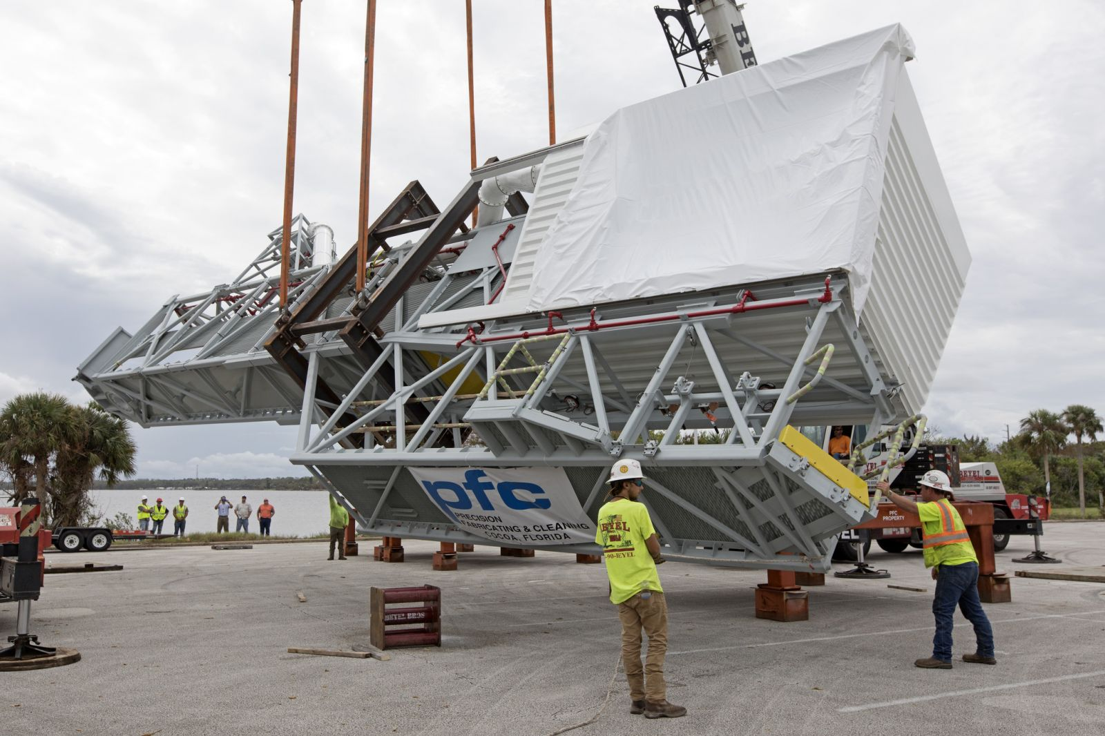 Workers help guide the Crew Access Arm onto a work stand after it arrives at NASA's Kennedy Space Center. Photo credit: NASA / Kim Shiflett