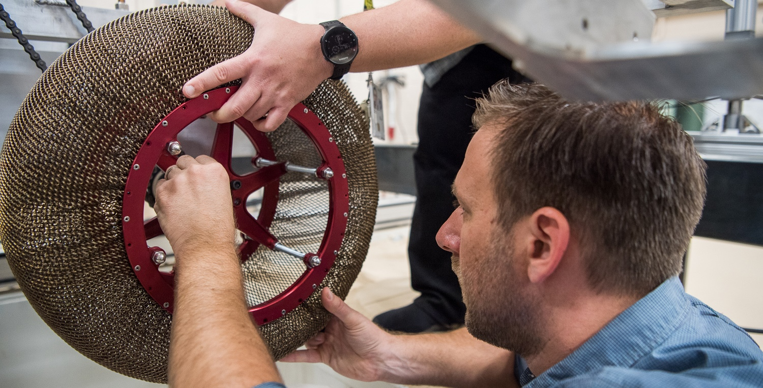 Engineer Colin Creager works on the latest design of a shape-memory alloy spring tire at the Simulated Lunar Operations (SLOPE) Lab at the NASA Glenn Research Center in Cleveland, Ohio. The new tire is designed for future rovers on Mars. Photo Credit: NASA Glenn
