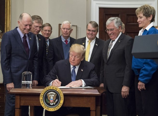 President Donald Trump signs Space Policy Directive 1 in December 2017, which directs NASA to return to the Moon. Standing alongside him in the White House's Roosevelt room were members of the Senate, Congress, NASA, and commercial space companies. Photo Credit: Aubrey Gemignani / NASA