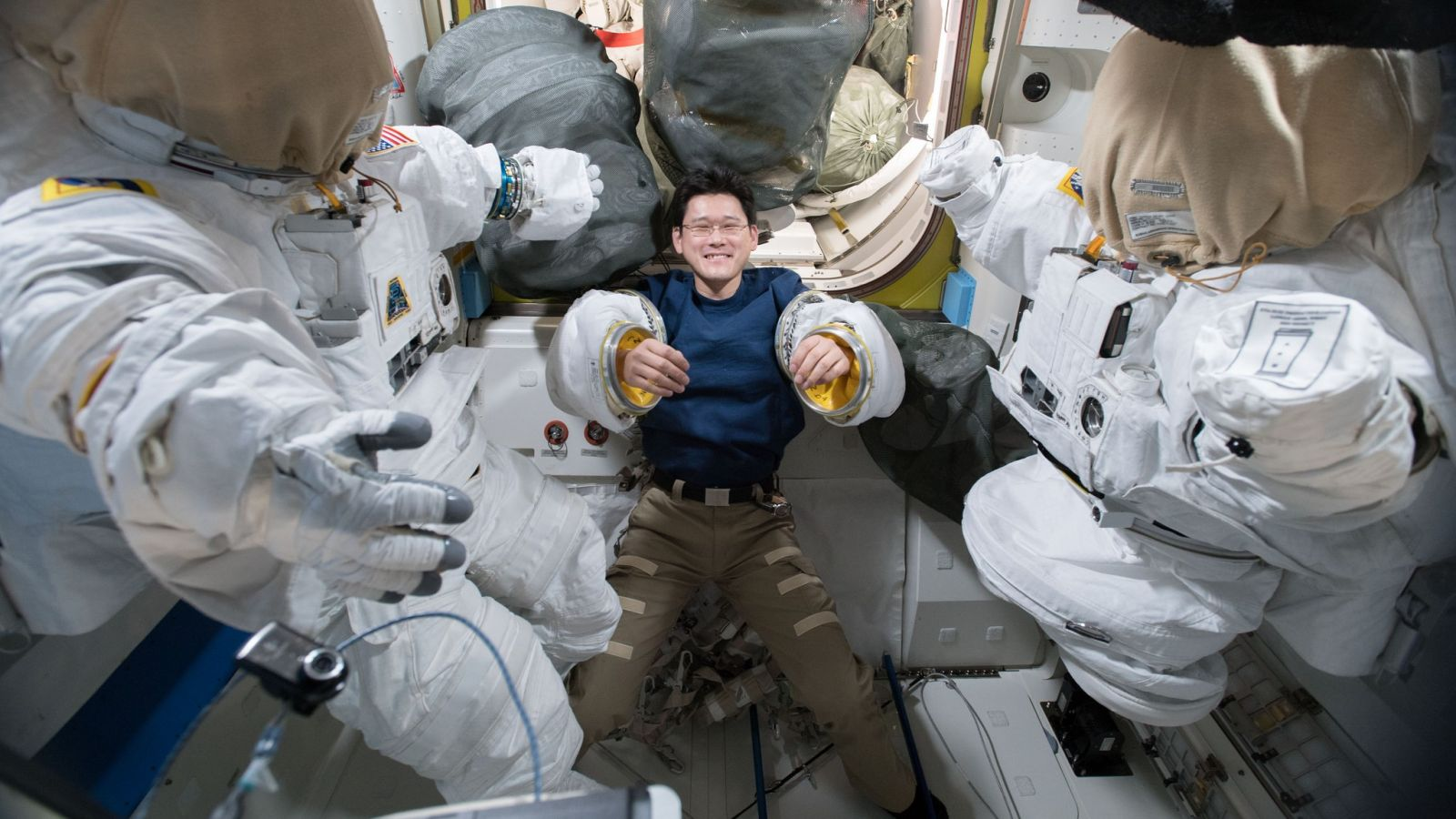 Japan Aerospace Exploration Agency astronaut Norishige Kanai tries on spacesuit sleeves inside the Quest airlock in preparation for the eventual U.S. EVA-48. Photo Credit: NASA