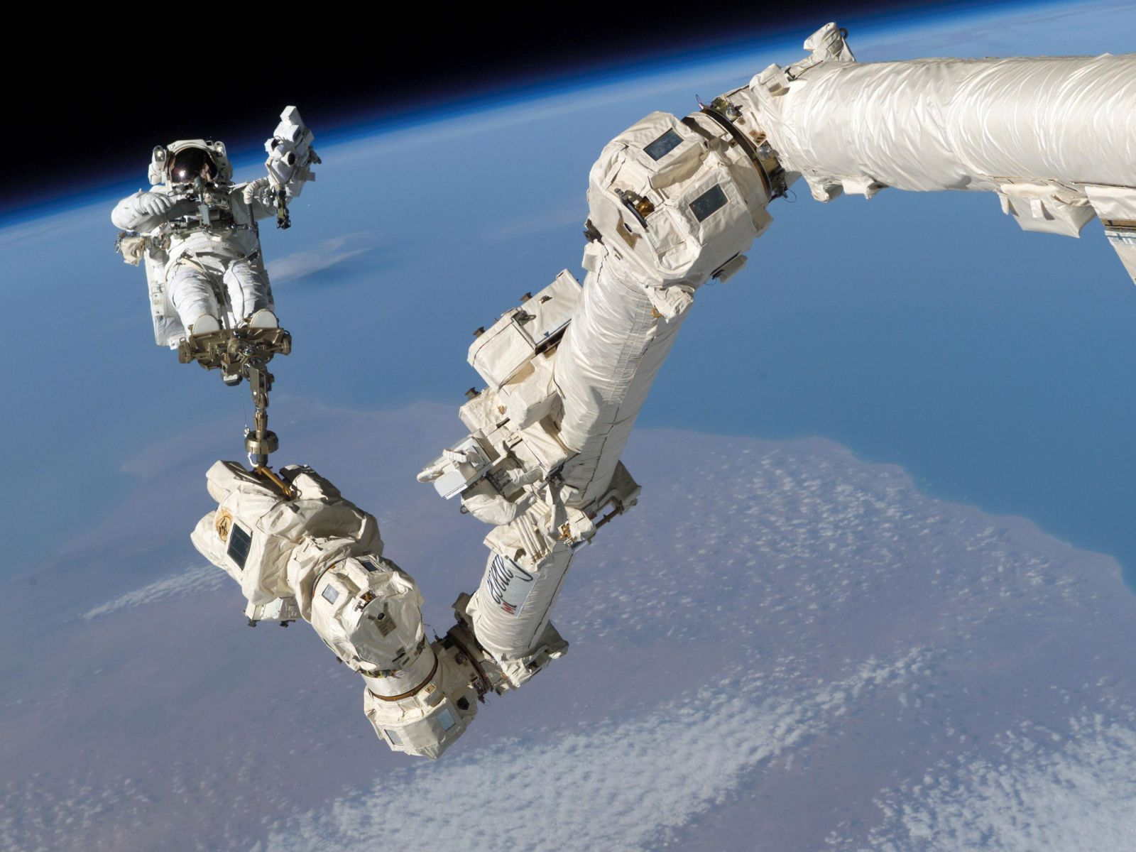 NASA astronaut Steve Robinson rides Canadarm2 to a work area in a spacewalk during the STS-114 mission to the International Space Station in 2005. Photo Credit: NASA