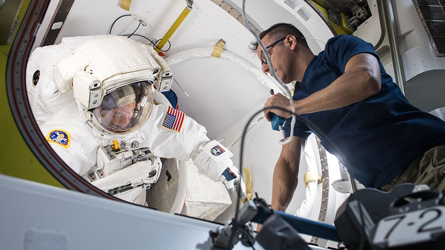 NASA astronaut Joe Acaba works to fit-check Scott Tingle's space suit before U.S. EVA-47. Photo Credit: NASA