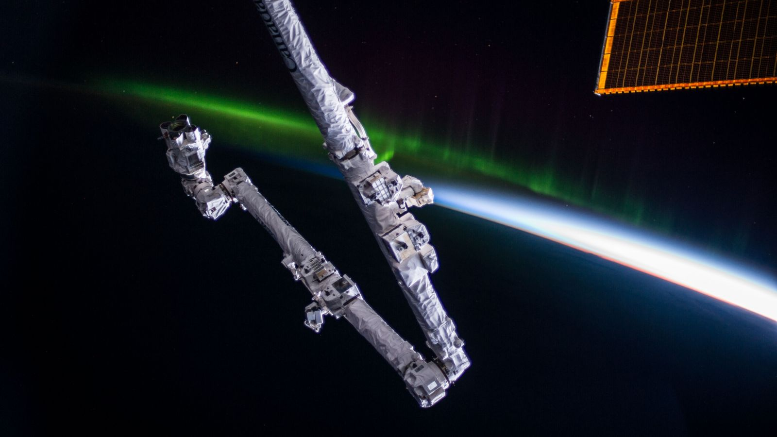 Canadarm2 attached to the ISS with an aurora in the background. Photo Credit: NASA