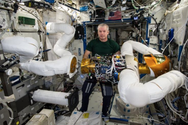 "Expedition 40 commander Steve Swanson performs ""robot surgery"" in a very complex on-orbit upgrade of Robonaut2 during the summer of 2014. Photo Credit: NASA"