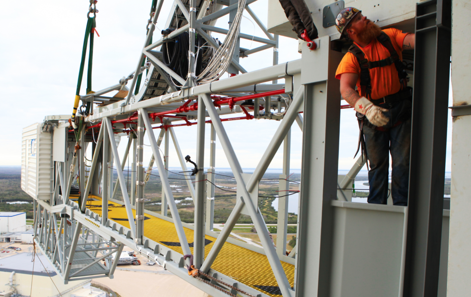 A worker begins installing the Orion crew access arm onto the launch tower. Photo Credit: Bill White / NASA