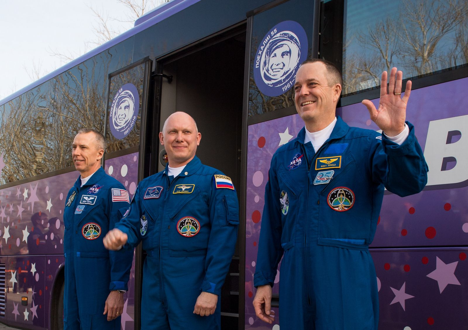 NASA's Drew Feustel, left, Russia's Oleg Artemyev, center, and NASA's Ricky Arnold wave to their friends and family in a final farewell in advance of their five month stay in space. Photo Credit: Joel Kowsky / NASA