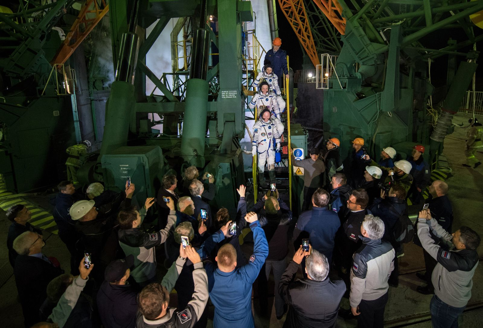 The Soyuz MS-08 crew waves goodbye at the base of the Soyuz-FG rocket. Photo Credit: Joel Kowsky / NASA