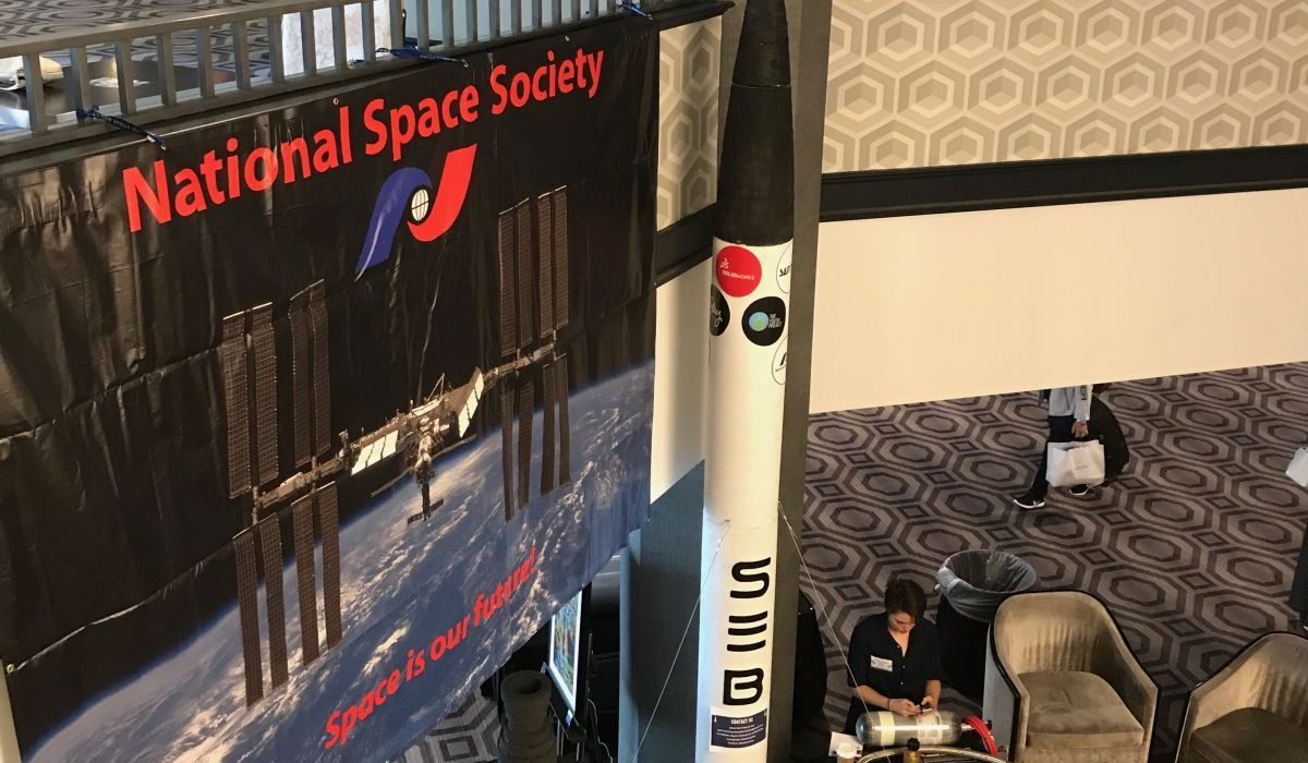 A two-thirds scale model of Berkley's liquid propellant rocket is displayed next to a banner for ISDC 2018.
