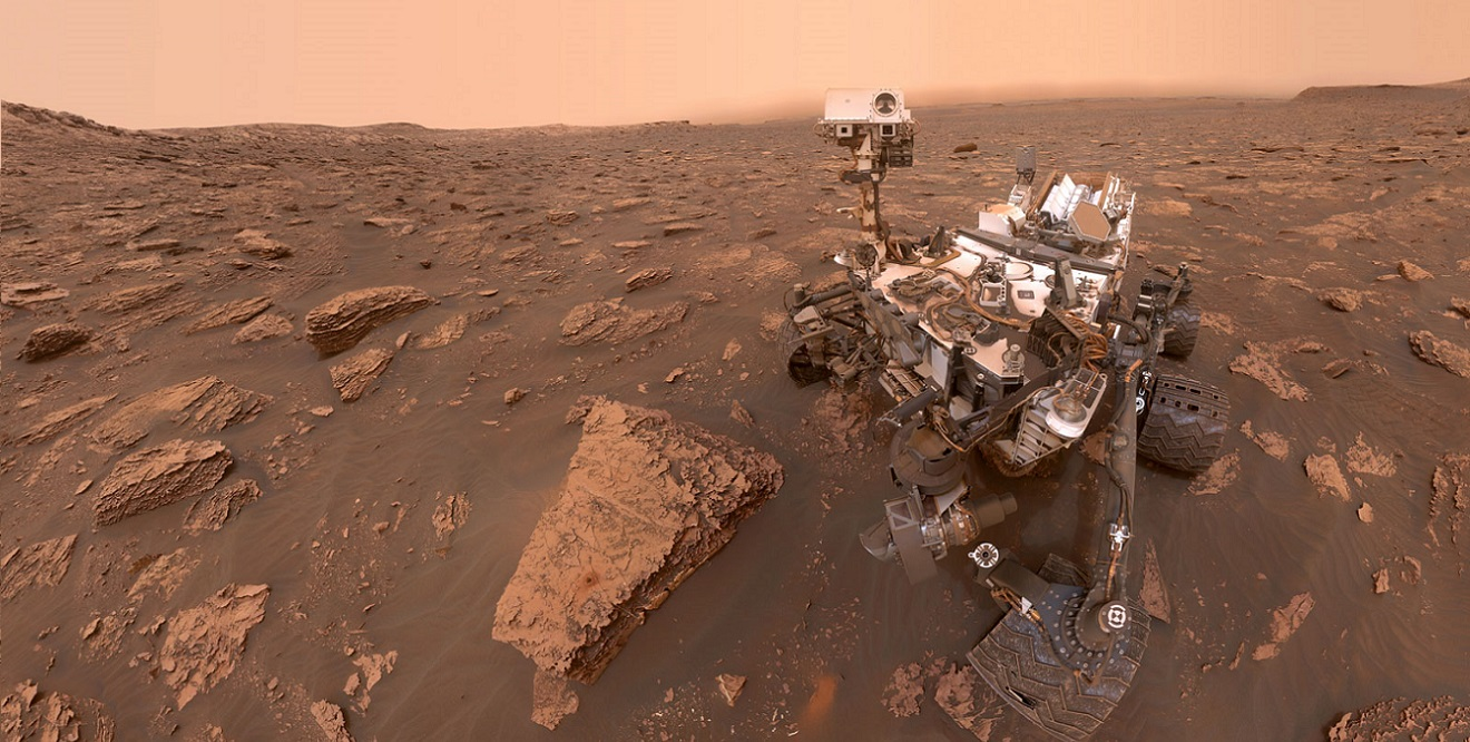 "A self-portrait by NASA's Curiosity rover taken on Sol 2082 (June 15, 2018). At the time of the picture, a Martian dust storm had reduced sunlight and visibility at the rover's location in Gale Crater. A drill hole can be seen in the rock to the left of the rover at a target site called ""Duluth."" Image Credit: NASA / JPL-Caltech/MSSS"
