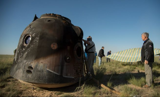 Russian search and rescue teams work to extract the crew from the capsule. Photo Credit: Bill Ingalls / NASA