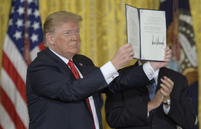 President Trump holds up the signed Space Policy Directive-3 during the June 18, 2018, meeting of the National Space Council. Photo Credit: Bill Ingalls / NASA