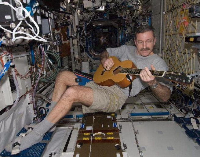 Burbank plays guitar during one of his stints on the International Space Station. Photo Credit: NASA