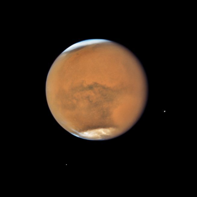 NASA's Hubble Space Telescope photographed Mars on July 18, 2018 as it neared its closest approach to Earth since 2003. It was just 36.9 million miles from Earth. It's springtime in southern hemisphere, where a dust storm ballooned into a global event in mid-June blanketing the planet. Even so, you can make out Hellas Basin, the bright, large oval area at the lower right. The orange area in the upper center of the image is Arabia Terra. South of that site, running east to west along the equator, are the long dark features known as Sinus Sabaeus (to the east) and Sinus Meridiani (to the west). Opportunity landed in the western portion of Sinus Meridiani, while her twin, Spirit, landed on the other side of the planet in Gusev Crater. The two small moons of Mars, Phobos (right) and Deimos (left), appear in the lower half of the image. Image Credit: NASA