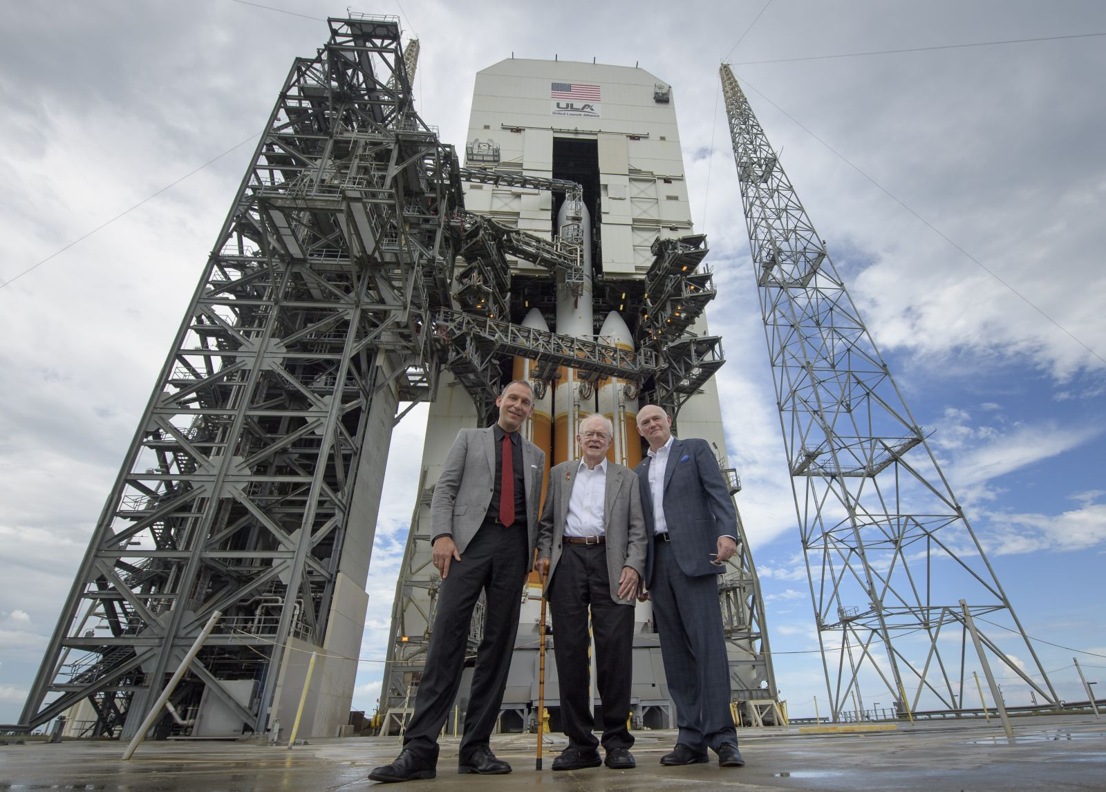 NASA Associate Administrator for the Science Mission Directorate Thomas Zurbuchen, left, American solar astrophysicist, and professor emeritus at the University of Chicago, Eugene Parker, center, and President and Chief Executive Officer for United Launch Alliance Tony Bruno pose for a group photo in front of the ULA Delta IV Heavy rocket with NASA's Parker Solar onboard, Friday, Aug. 10, 2018, Launch Complex 37 at Cape Canaveral Air Force Station, Florida. This is the first NASA mission that has been named for a living individual. Parker Solar Probe is humanity's first-ever mission into a part of the Sun's atmosphere called the corona. Here it will directly explore solar processes that are key to understanding and forecasting space weather events that can impact life on Earth. Photo Credit: Bill / Ingalls
