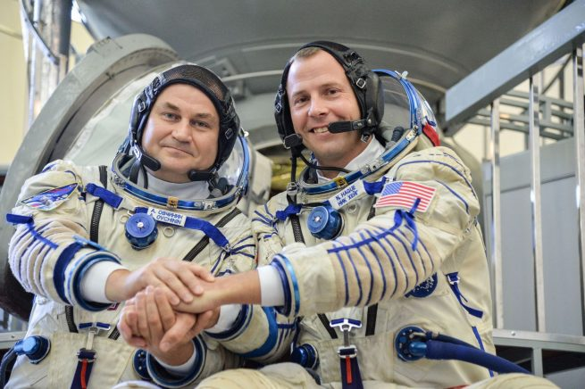 As an example of the decades-old partnership with Roscosmos and NASA, Russian cosmonaut Alexey Ovchinin and American astronaut Nick Hague pose in front of a Soyuz mockup on Sept. 14 during their qualification exams. The two are training for their flight to the International Space Station, which is expected to launch on Oct. 11, 2018. Photo Credit: Sarah Volkman / NASA