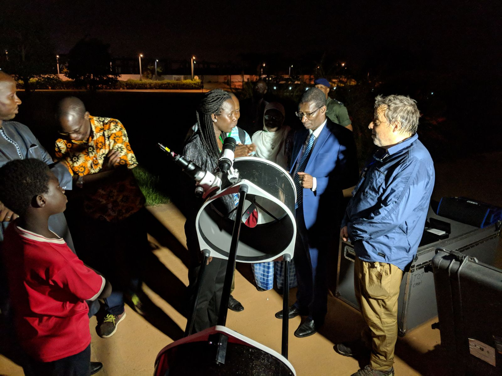 Occultation team members François Colas at right, of the Observatoire de Paris, France, and Salma Sylla Mbaye at center left, of Cheikh Anta Diop University, Dakar, Sénégal, show their telescope to Mary Teuw Niane, center right, the Sénégalese Minister of Higher Education, Research, and Innovation or MESRI, at one of the practice sessions held near Dakar before the stellar occultation by Ultima Thule, while other visitors (left) look on. Photo Credit: NASA/Johns Hopkins University Applied Physics Laboratory/Southwest Research Institute/Mike Grusin