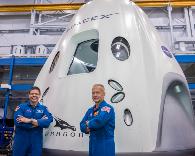 Bob Behnken, left, and Doug Hurley stand in front of a mockup of SpaceX's Crew Dragon spacecraft. Photo Credit: NASA