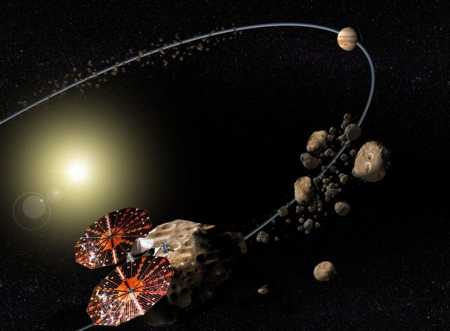 Artist's depiction of the Lucy spacecraft studying Trojan asteroids orbiting with Jupiter. Image Credit: NASA