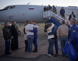 Expedition 57 Flight Engineer Alexey Ovchinin of Roscosmos, left, and Flight Engineer Nick Hague of NASA, right. embrace their families after landing at the Krayniy Airport, Thursday, Oct.11, 2018 in Baikonur, Kazakhstan. Hague and Ovchinin arrived from Zhezkazgan after Russian Search and Rescue teams brought them from the Soyuz landing site. During the Soyuz MS-10 spacecraft's climb to orbit, an anomaly occurred, resulting in an abort downrange. The crew was quickly recovered and is in good condition. Photo & Caption Credit: Bill Ingalls / NASA