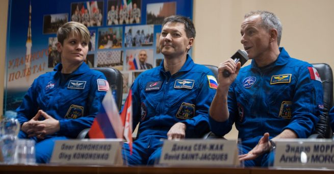 NASA astronaut Anne McClain, left, Russian cosmonaut Oleg Kononenko, center, and Canadian Space Agency astronaut David Saint-Jacques answer questions during a pre-launch press conference in Baikonur Cosmodrome, Kazakhstan. Photo Credit: Aubrey Gemignani / NASA