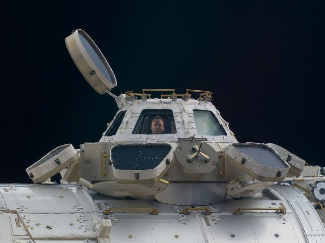 NASA astronaut Ron Garan looks out of a window on the Cupola module during Expedition 28 in 2011. Photo Credit: NASA