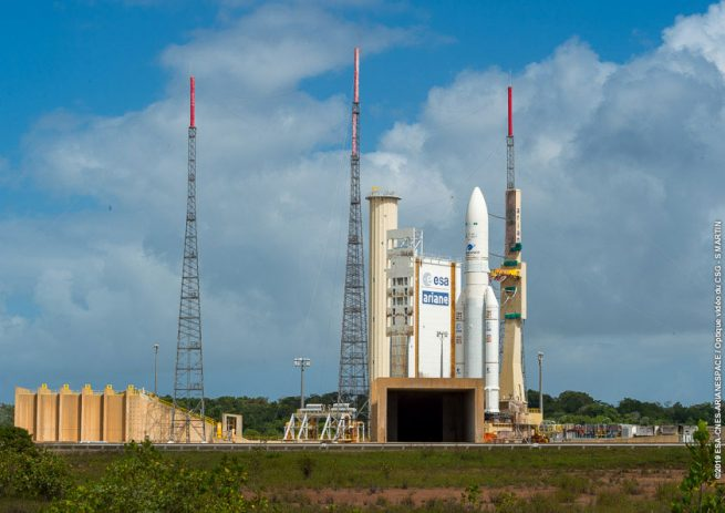 The Ariane 5 rocket with the Saudi Geostationary Satellite 1/Hellas Sat 4 and GSAT-31 satellites encapsulated stands at the launch pad in advance of its liftoff. Photo Credit: Arianespace