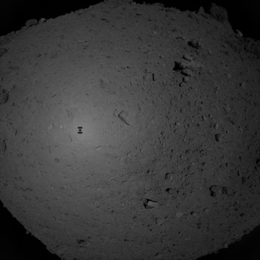 Hayabusa-2 descends toward Ryugu before briefly touching the surface of the asteroid. Its shadow can be seen near the center of the image. Photo Credit: JAXA